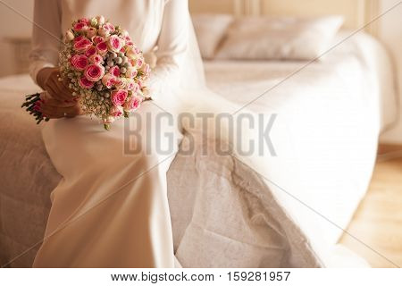Bride sitting in the bed holding the bouquet in the white colored room. Selective focus