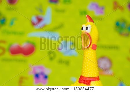 Toy Rubber Shriek Yellow Chicken On Blur Toy Background In Messy Room.