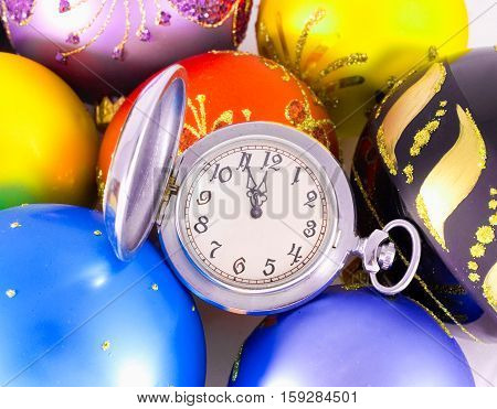 Pocket watch showing almost twelve o'clock (five minutes to the midnight) and multicolored Christmas balls New Year concept