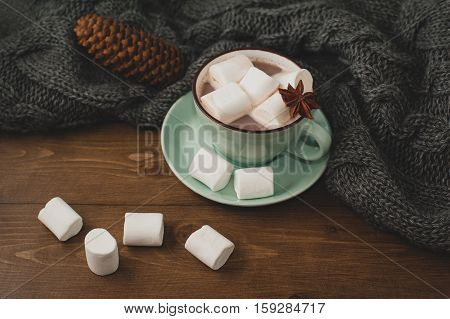 winter home background - cup of hot cocoa with marshmallow and warm dray knitted sweater on wooden background.