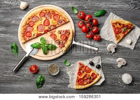 Delicious pizza with slices and ingredients on table