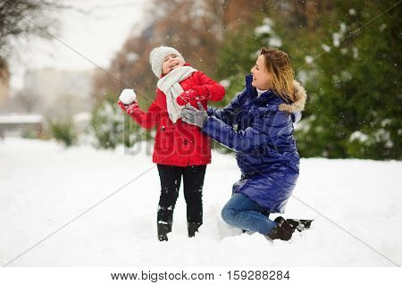 Mother and daughter cheerfully spend time in winter day. They walk in the snow-covered park. Girl throws into someone a snowball. Mother has sat down near daughter and smiles. It is snowing.
