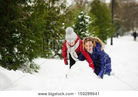 Mother with daughter build a snowman in park. It is snowing. All ground in park is completely covered with fluffy snow. Woman and girl are dressed in bright down-padded coats. They have joyful faces.