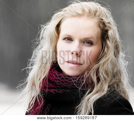 portrait of blond woman with blue eyes on a dark background winter girl in a black coat, curly hair, blond and beautiful, red scarf, light snow, cute look, half-smile, the kindness, photo on street,