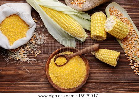 Corn seeds and groats on wooden table