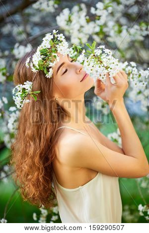 Young Beautiful Woman In White Dress Enjoying Smell Of Blooming Tree On A Sunny Day. Close Eyes