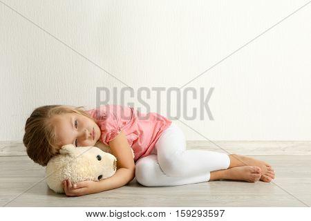 Sad little girl with teddy bear lying on floor in empty room