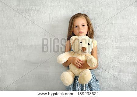 Cute little girl with teddy bear against grey wall