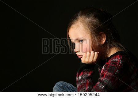 Sad little girl on black background