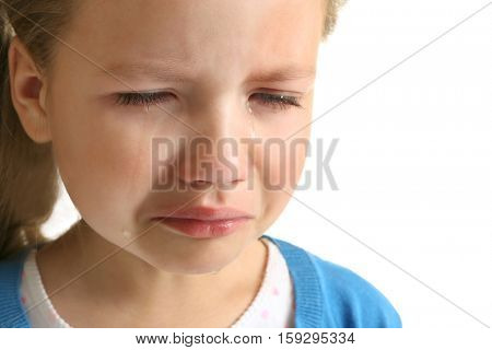 Portrait of crying little girl on white background, close up view
