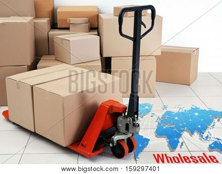 Hand palette truck with cardboard boxes at storehouse. Wholesale and logistics concept.
