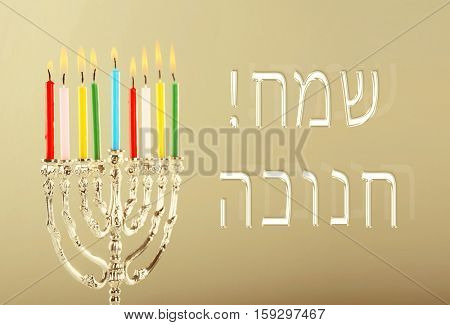 Menorah with candles for Hanukkah on color background. Hanukkah celebration concept. Text HAPPY HANUKKAH in Hebrew
