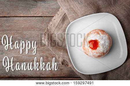 Plate with tasty doughnut on wooden background. Hanukkah celebration concept. Text HAPPY HANUKKAH