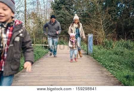 Happy family running and having fun together over a wooden pathway into the forest