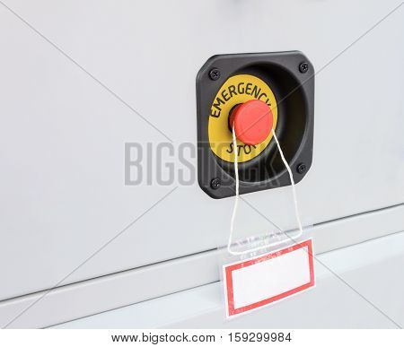Red button emergency stop equipment. Under the button is suspended empty plate. The white rectangular plate with a red border around the perimeter.