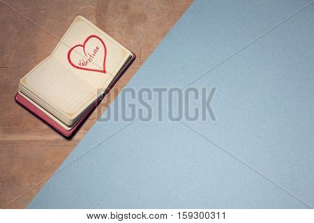 Opened Notebook On Wooden Background And With Picture Of Heart On Page;
