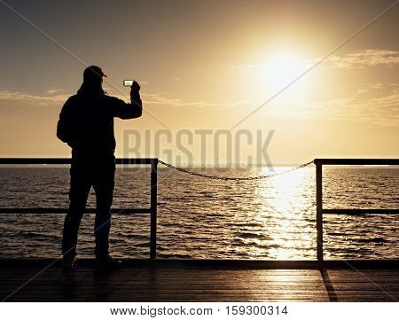 Man At Handrail On Mole Take Photos Over Sea To Morning Horizon. Tourist Photograph