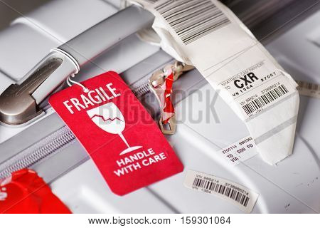 Luggage Tag (fragile) Attached To White Suitcase At Airport