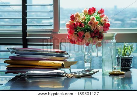 Documents and equipments on wood table against the windows with blur cityscape background Office workplace concept