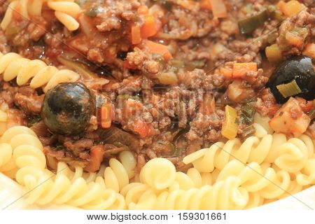 Pasta on a plate: Fusilli with ragu cheese and black olives