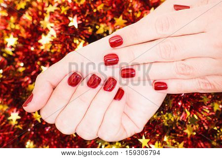 Closeup of caucasian female hands with professional red manicure with glittering sparkles isolated on Christmas background. Modern festive gel polish with base coat first and top cure with LED lamp