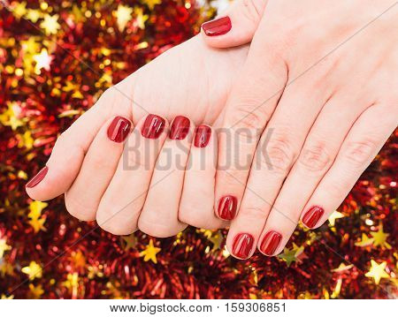 Close up of caucasian female hands with professional red manicure with glittering sparkles isolated on Christmas background. Modern festive gel polish with base coat first and top cure with LED lamp