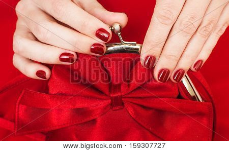 Beautiful small red female purse in hands of young woman and red evening dress. Accessory and clothes perfectly matching to each other. Fingernails with beautiful professional red manicure. Flat lay.