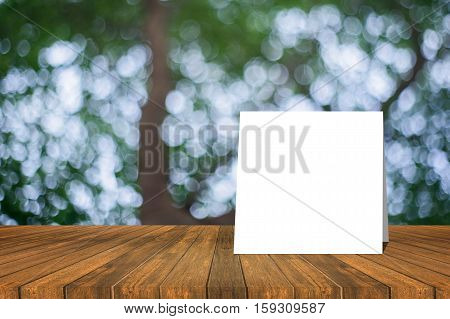 White Card Put On Wooden Desk Or Wooden Floor On Green Bokeh Background.use For Present Or Mock Up Y