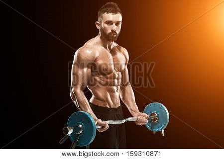 Close up of young muscular man lifting weights over dark background. with sun flare