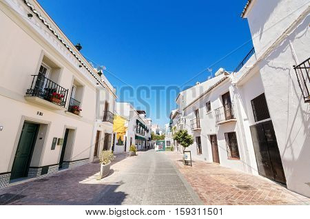 Typical street with white houses in the touristic village of Nerja Malaga Spain.