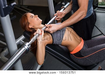 happy cutie athletic girl , with instructor execute exercises barbell and smile, in sport-hall
