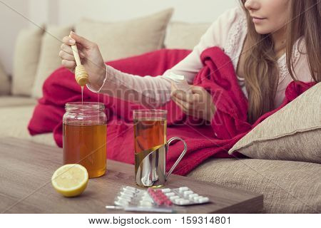 Sick woman lying in bed with high fever and a flu putting some honey in her tea. Lemon honey jar and pills set around the table focus on the honey spoon