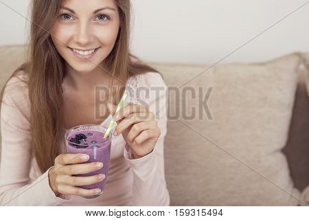 Beautiful girl sitting on a living room couch smiling and holding a glass of raspberry smoothie