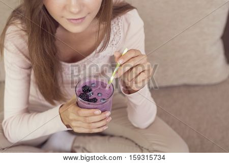 Beautiful girl sitting on a living room couch smiling and holding a glass of raspberry and blueberry smoothie. Focus on the smoothie
