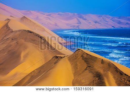 The west coast of the Atlantic Ocean. Giant moving sand dunes. Sandwich Harbour - part of Namib-Naukluft National Park, Namibia