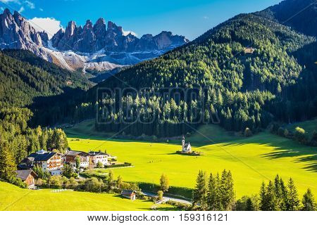The symbol of valley Val di Funes - church of Santa Maddalena. Rocky peaks and forested mountains surrounded by green Alpine meadows. Sunny warm day in Dolomites, Tirol