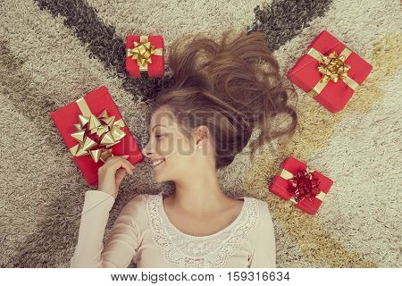 Top view of a young woman lying on the carpet surrounded with nicely wrapped presents