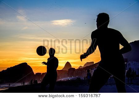 Beautiful sunset and silhouettes of men playing dar toques na bola game at Copacabana beach, Rio de Janeiro, Brazil