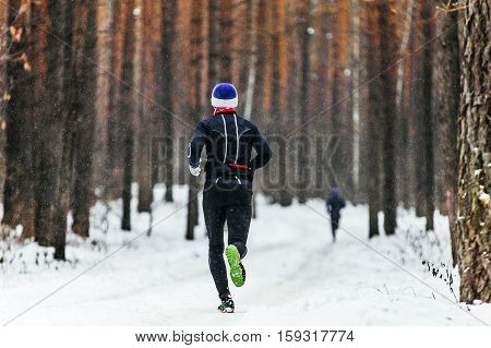 male athlete runner running in falling snow in forest in marathon winter