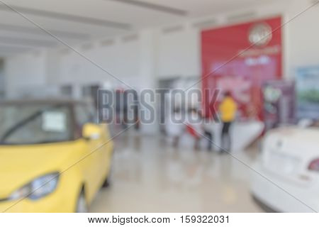 Background blur of car and showroom.Businessmen blur in the workplace.abstract blur background work in office with car.Abstract background of office. shallow depth of focus.auto motor sale shop color