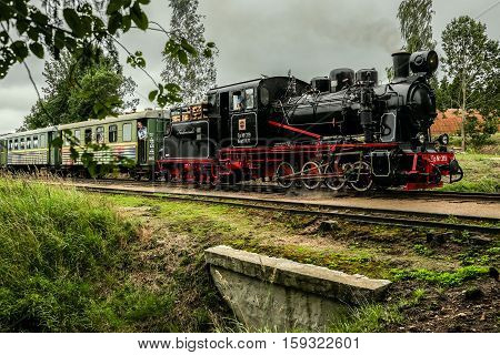 Aluksne Latvia - August 6 2016: Real narrow-gauge railway steam locomotive driving over a small bridge with passengers aboard