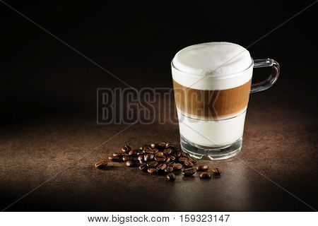 Glass of hot Latte macchiato coffee close up