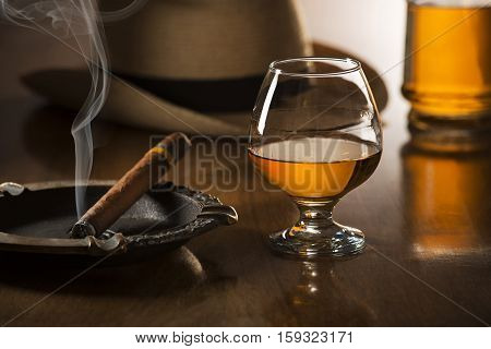 Whiskey cognac brandy and cigar on wooden background
