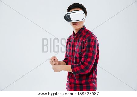 Image of young man dressed in casual shirt in a cage and wearing virtual reality device and holding an imagine tennis racket. Isolated over white background.