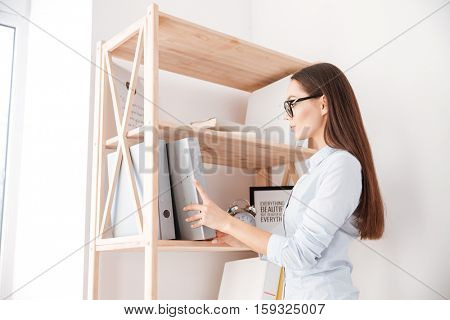 Young casual businesswoman taking folder from a book shelf while standing in office