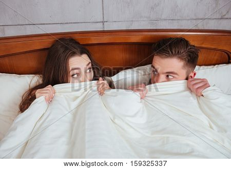 Photo of confused young woman and her man looking at each other while lying in bed under blanket