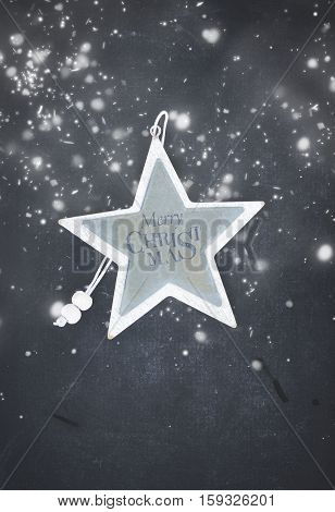 Merry Christmas star on black wooden background with snow