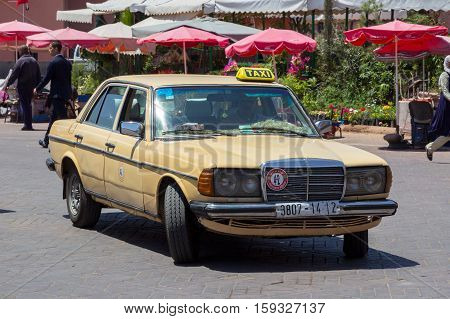 MARRAKECH MOROCCO - APR 29 2016: Old Mercedes-Benz taxi driving on the Djemaa-el-Fna in Marrakech.