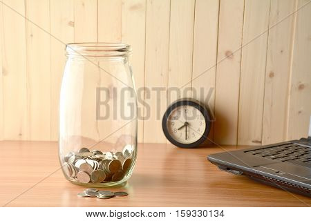 The coin inside of bottle ,alarm clock and lap top on the wood table.