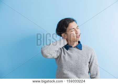 man student feel shoulder pain with blue background asian